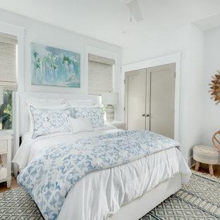 Foto di una grande camera degli ospiti tropicale con pareti bianche, parquet chiaro e pavimento blu