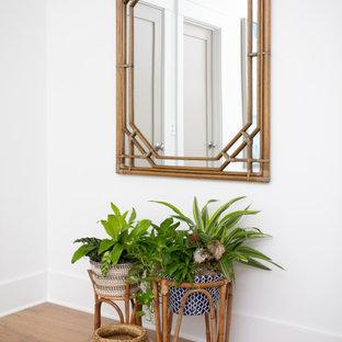 Ejemplo de habitación de invitados exótica, grande, con paredes blancas, suelo de madera clara y suelo azul
