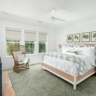 Modelo de dormitorio principal, tropical, grande, con paredes blancas, suelo de madera clara y suelo verde