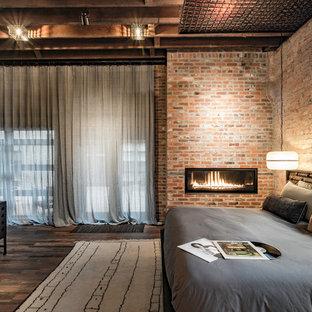 デンバーのインダストリアルスタイルのおしゃれな主寝室 (赤い壁、濃色無垢フローリング、横長型暖炉、金属の暖炉まわり) のインテリア