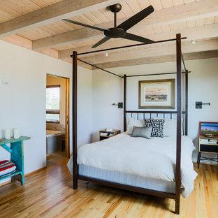 サンタフェスタイルのおしゃれな寝室 (白い壁、淡色無垢フローリング、茶色い床) のインテリア