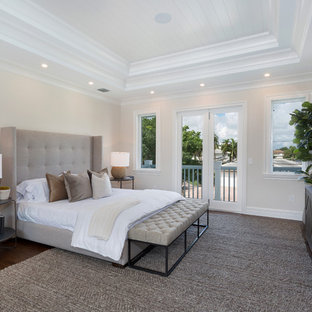 Large coastal master dark wood floor and brown floor bedroom photo in Other with beige walls and no fireplace