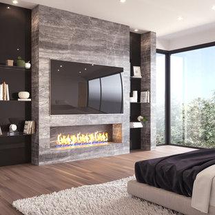 Modelo de dormitorio principal y abovedado, moderno, de tamaño medio, con paredes beige, suelo de baldosas de porcelana, chimenea tradicional, suelo gris y marco de chimenea de piedra