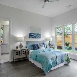Example of a farmhouse guest gray floor bedroom design in Austin with white walls