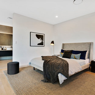Contemporary master bedroom in Sunshine Coast with white walls, light hardwood floors and beige floor.