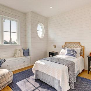 Maritimes Schlafzimmer mit weißer Wandfarbe, braunem Holzboden, braunem Boden und Holzdielenwänden in Los Angeles