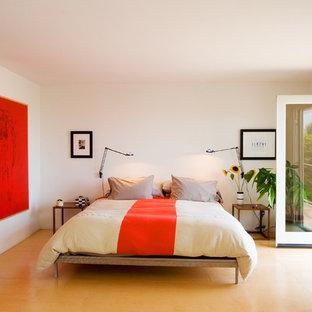 Immagine di una camera da letto minimal con pareti bianche e pavimento giallo