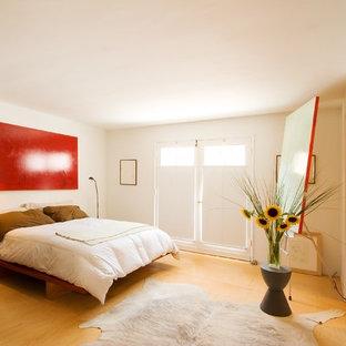Immagine di una camera da letto design con pavimento in compensato e pavimento giallo
