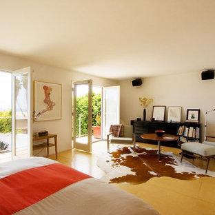 На фото: хозяйская спальня в современном стиле с белыми стенами, полом из фанеры и желтым полом без камина с