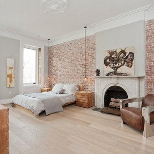 Ejemplo de dormitorio principal, nórdico, grande, con paredes grises, suelo de madera clara, chimenea tradicional y marco de chimenea de piedra