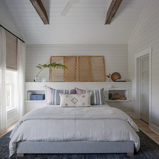 Example of a large coastal master light wood floor and brown floor bedroom design with white walls and no fireplace