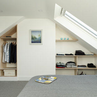 Small contemporary bedroom in Sussex with white walls, carpet and grey floors.