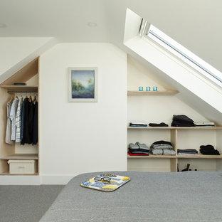 Modelo de dormitorio actual, pequeño, con paredes blancas, moqueta y suelo gris