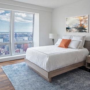 Bedroom - small contemporary dark wood floor and brown floor bedroom idea in New York with white walls