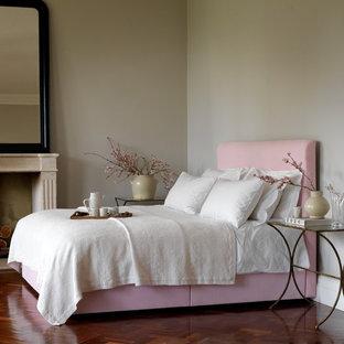 Imagen de dormitorio exótico con paredes grises, suelo de madera en tonos medios y chimenea tradicional