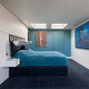 Immagine di una grande camera degli ospiti moderna con pareti blu, moquette, camino lineare Ribbon, cornice del camino in intonaco e pavimento nero