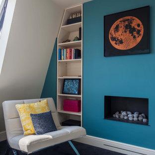 Ejemplo de dormitorio principal, moderno, grande, con paredes azules, moqueta, chimenea tradicional, marco de chimenea de yeso y suelo negro