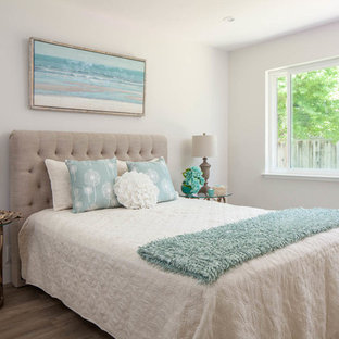 Design ideas for a mid-sized arts and crafts guest bedroom in San Francisco with white walls, laminate floors and brown floor.