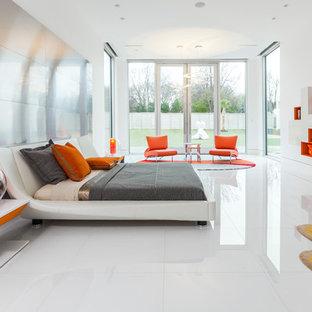 На фото: хозяйская спальня в современном стиле с белыми стенами, белым полом и кроватью у окна без камина
