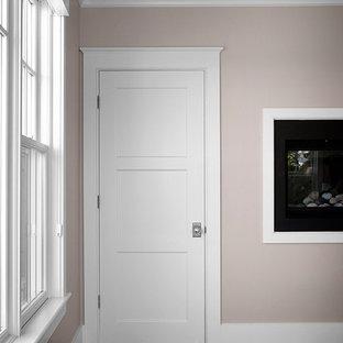 Immagine di una grande camera matrimoniale stile marinaro con pareti beige, parquet scuro, camino lineare Ribbon, cornice del camino in intonaco e pavimento marrone