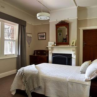 Modelo de dormitorio principal, vintage, de tamaño medio, con paredes beige, moqueta, chimenea tradicional y marco de chimenea de madera