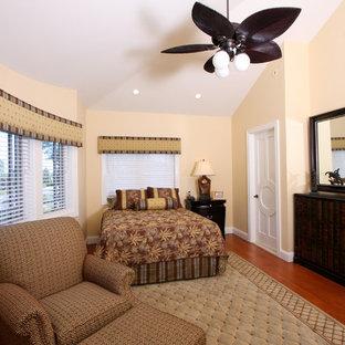 ニューヨークの中くらいのトロピカルスタイルのおしゃれな主寝室 (黄色い壁、無垢フローリング) のインテリア