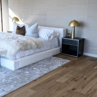Modelo de dormitorio principal, moderno, grande, con paredes blancas, suelo de madera clara, chimenea tradicional, marco de chimenea de ladrillo y suelo marrón