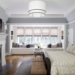 Photo of a large traditional master bedroom in New York with grey walls, medium hardwood floors and a standard fireplace.