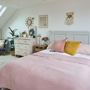 Photo of a traditional bedroom in London with white walls, medium hardwood flooring and brown floors.