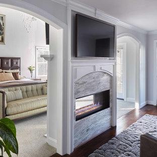 Mittelgroßes Klassisches Hauptschlafzimmer mit grauer Wandfarbe, dunklem Holzboden, braunem Boden, Tunnelkamin und Kaminumrandung aus Stein in Raleigh