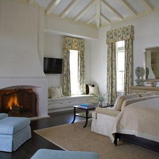 Idéer för stora medelhavsstil huvudsovrum, med vita väggar, mörkt trägolv, en standard öppen spis och en spiselkrans i gips
