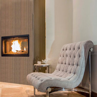 Inspiration for a large contemporary master bedroom in San Diego with grey walls, limestone floors and a two-sided fireplace.