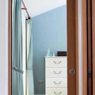 Modelo de habitación de invitados campestre, extra grande, con paredes azules, suelo de madera clara y suelo amarillo