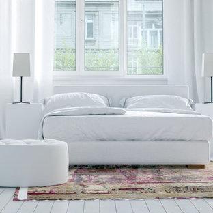 Idee per una grande camera matrimoniale nordica con pareti bianche, pavimento in legno verniciato, camino classico, cornice del camino in intonaco e pavimento bianco