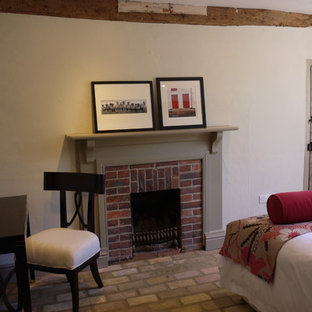 Example of a mid-sized farmhouse guest brick floor bedroom design in Hampshire with beige walls