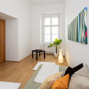 Immagine di una piccola camera degli ospiti design con pareti bianche, pavimento in compensato e nessun camino