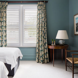 Design ideas for a classic guest bedroom in London with blue walls, carpet, a standard fireplace and white floors.