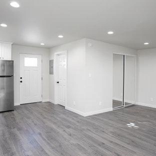 Imagen de dormitorio tipo loft, moderno, de tamaño medio, sin chimenea, con paredes blancas, suelo vinílico y suelo gris