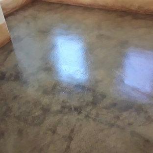 アルバカーキの広いラスティックスタイルのおしゃれな客用寝室 (白い壁、コンクリートの床、暖炉なし、コンクリートの暖炉まわり、茶色い床)