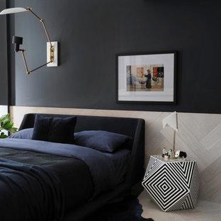 Imagen de dormitorio contemporáneo con paredes negras, suelo de madera clara y suelo gris