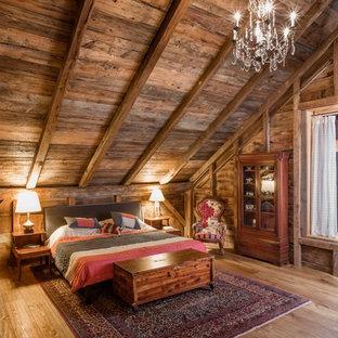 Ejemplo de dormitorio principal, rural, grande, sin chimenea, con paredes marrones, suelo de madera oscura y suelo marrón