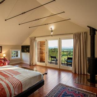 Стильный дизайн: хозяйская спальня в стиле кантри с бежевыми стенами, паркетным полом среднего тона, печью-буржуйкой и фасадом камина из камня - последний тренд