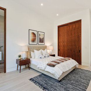 Example of a large trendy master light wood floor and beige floor bedroom design in Los Angeles with white walls
