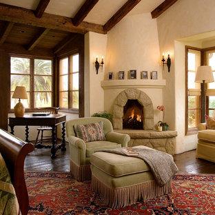 Modelo de dormitorio principal, de estilo americano, extra grande, con chimenea de esquina, paredes beige, suelo de madera oscura y marco de chimenea de piedra