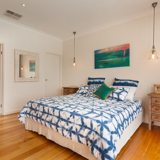 Inspiration for a mid-sized beach style guest bedroom in Other with white walls, medium hardwood floors and brown floor.