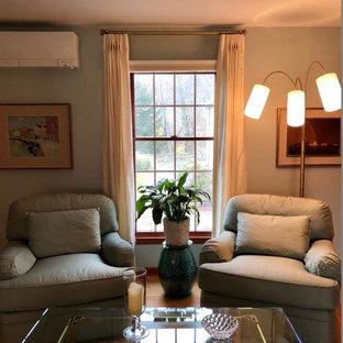 Ejemplo de dormitorio principal, actual, pequeño, con paredes azules, suelo de madera en tonos medios, chimenea tradicional, marco de chimenea de ladrillo y suelo marrón