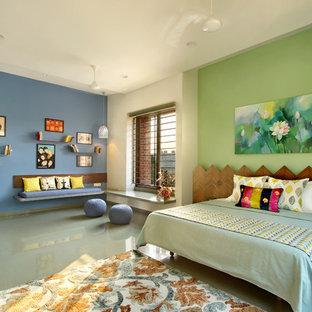 Foto di una camera da letto etnica con pareti blu, pavimento in cemento e pavimento grigio