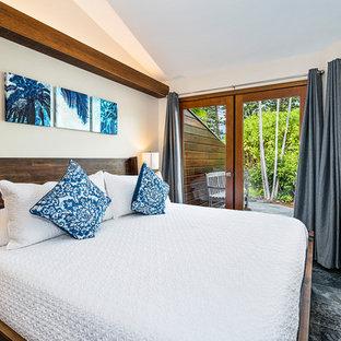 Modelo de habitación de invitados tropical, de tamaño medio, con paredes blancas, suelo de pizarra y suelo negro