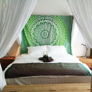 Ejemplo de dormitorio principal, ecléctico, de tamaño medio, con paredes blancas, suelo laminado y suelo marrón