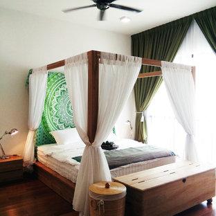 Modelo de dormitorio principal, tropical, de tamaño medio, con paredes blancas, suelo laminado y suelo marrón